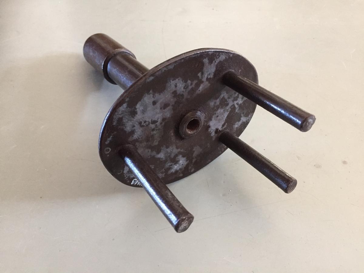 """Form: Rundt håndtak med oval plate. På platen er det montert 3 """"pigger""""."""