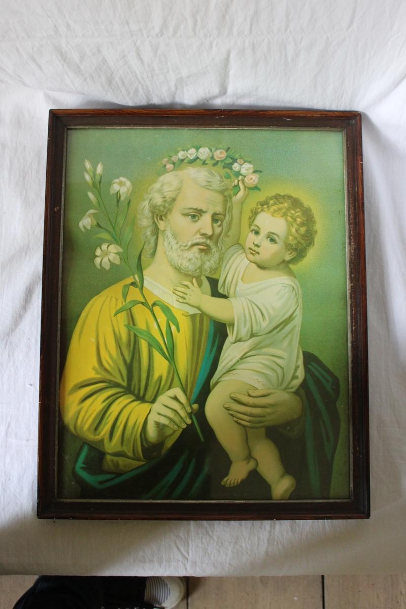 Religiöst motiv. Föreställer en man som i ena handen håller en liljekvist och med den andra bär ett barn som i sin tur håller en blomkrans som gloria över mannens huvud.