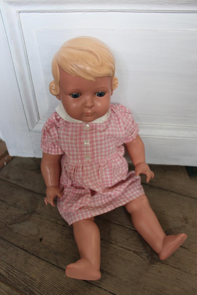 """Celluloiddocka """"Gunilla"""" 56cm från Shildkröt. Tillverkad i U.S. Zone i Tyskland. Dockan har rörliga armar och ben. Dockans ögon kan sluta sig och öppna sig beroende på om den ligger ner eller sitter upp. """"Gunilla"""" har blondt hår och blåa ögon.  På dockans övre del av ryggen och i nacken finns tillverkarens märke, en sköldpadda. På ryggen finns också numret """"56"""" som står för dockans längd."""