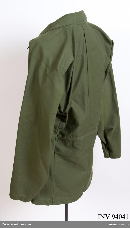 """Vapenrock av grönt bomullstyg, med blixtlåsknäppning och två bröstfickor med blixtlås. Vidhängande etikett: """"Prov på arbetsmodell, M 7351-, Teknisk bestämmelse gäller, Vapenrock m/ny, 1 prov"""". Etikett i nacken: """"FMV - A:IBP Försök"""". Etikett i nacken: """"184, 180-183, 60"""". Tillverkad av Norsel 1981, enligt suddig stämpel på insidan."""