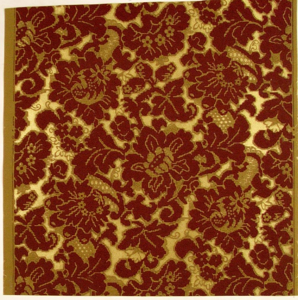 Ett ytfyllande silhuett-/blommönster i guld, senapsgult och vinrött.