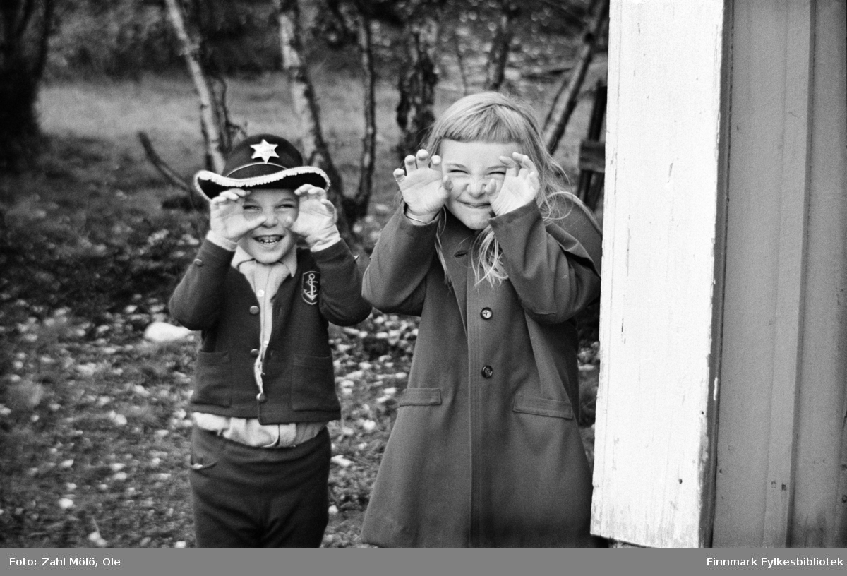 Fotoserie av fotograf Ole Zahl Mölö. Vadsø mai 1968. Familieportrett av fotografens barn Stig og Irma-Sofie. Ole Zahl Mölö, også kjent som Zahl Møller under hans tid i Vadsø – med kunstnernavnet OZAM – er født 8.juli i 1937, i Vadsø. Fotoarkivet har ca. 7500 negativer av Ole Zahl Mölös arbeider i sin samling. Bildematerialet inneholder motiv fra Vadsøs lokalmiljø og gjenspeiler hans hverdagsliv i byen og bymiljøet i vekst på 1960-70-tallet.