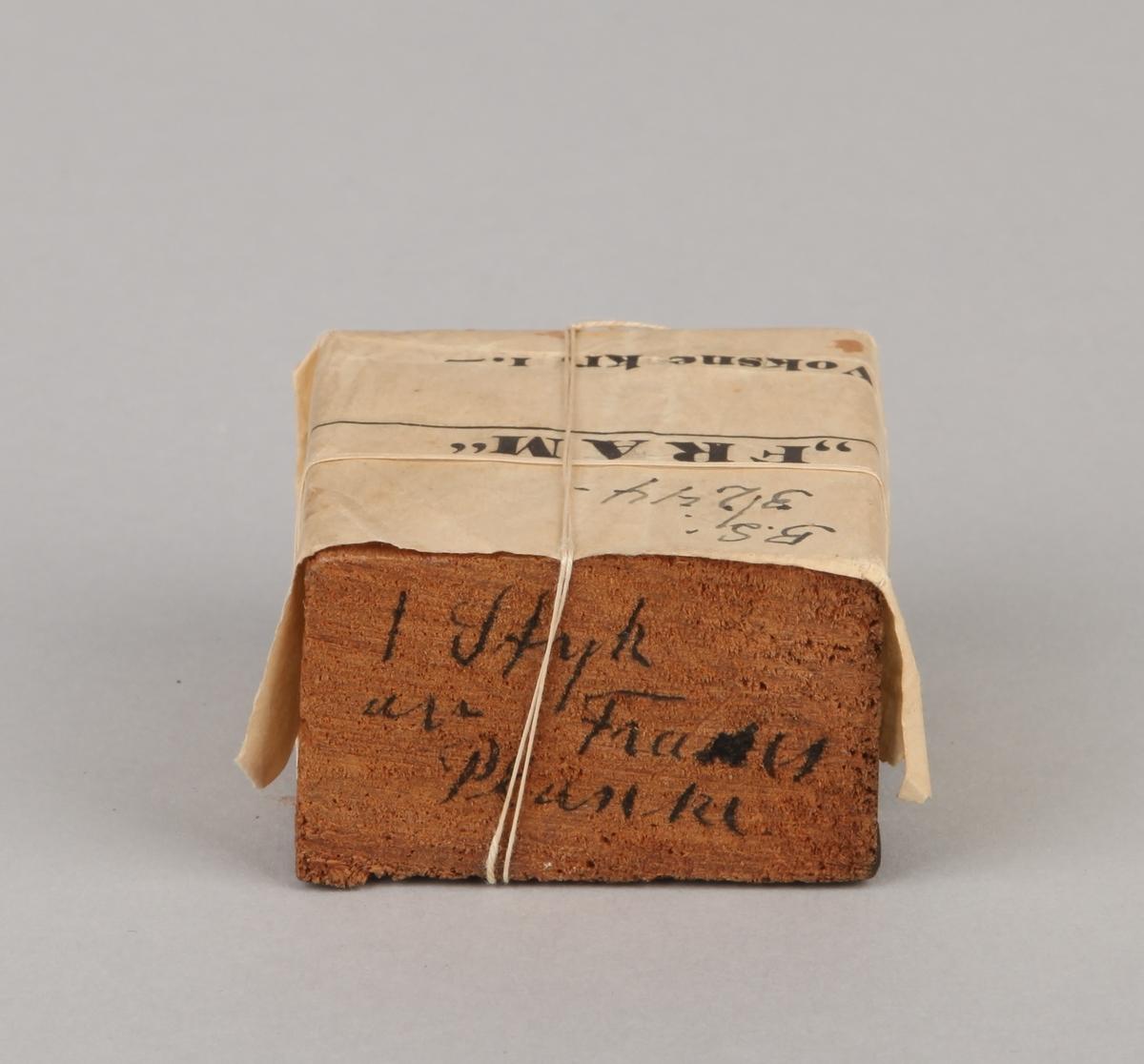 Trestykke/plankebit fra polarskuten FRAM. FRAM ble bygget av Colin Archer i samarbeid med Fridtjof Nansen som ville ha et spesialbygd fartøy til å seile over Polhavet med. Med en kvittering i papir merket nr. 841.