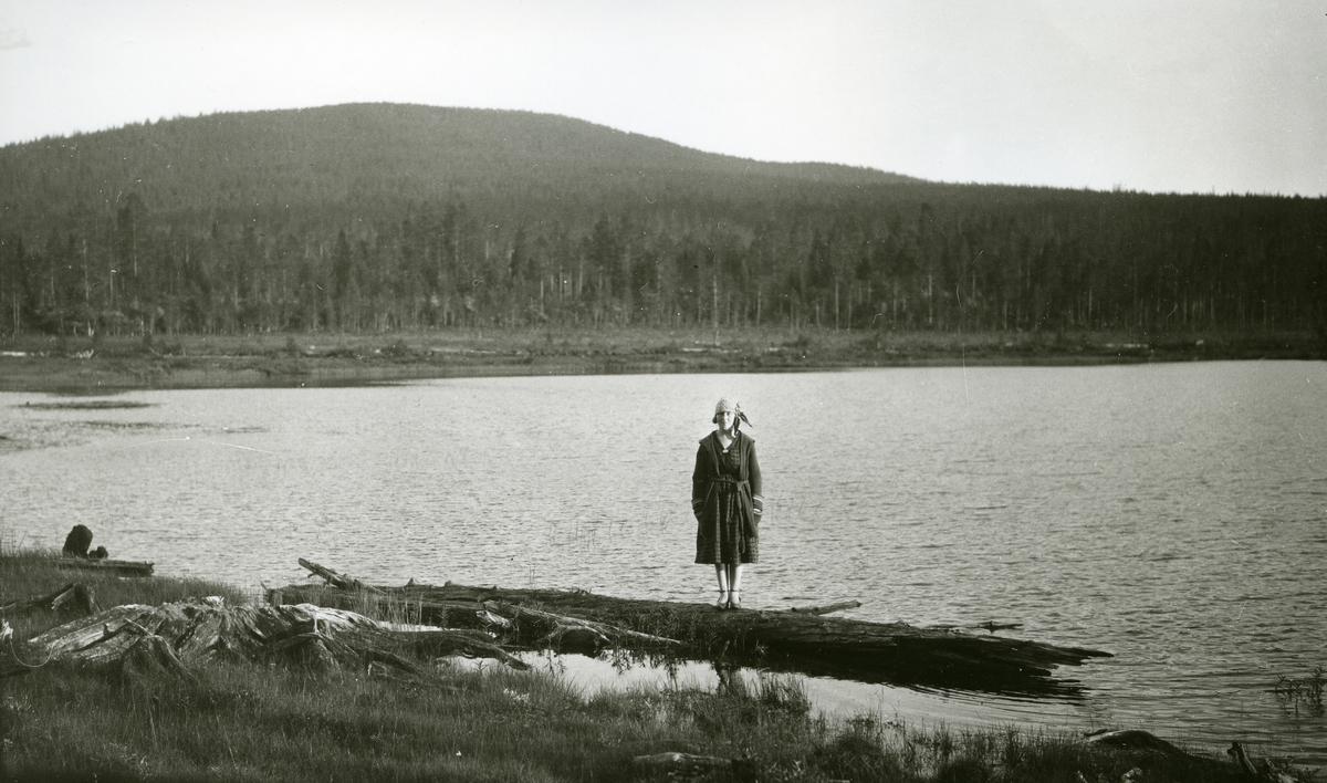 Kvinne stående på trestamme ved innsjø (Flersjøen).