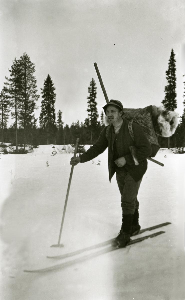 """Skiløper (skogsarbeider) i Galåsen med øksa under armen og """"neverkonten"""" på ryggen."""