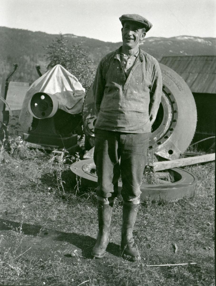 Ein mann med sikspens og gummistøvler står foran nokre bildekk.