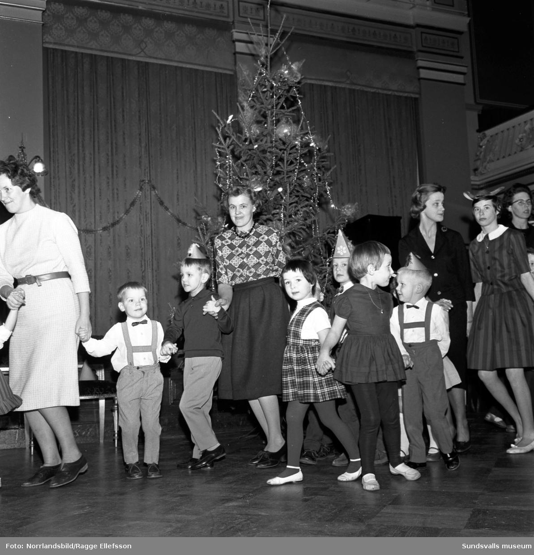 Barnfest till lucia i stadshuset för Stadshusrestaurangens anställdas barn. Glada finklädda barn med pappershattar och kalastutor dansar ringdans och poserar på gruppbild.