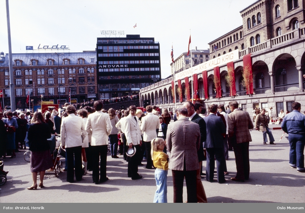"""torg, mennesker, 1. mai-feiring, kontorbygninger, Venstres Hus, politistasjon, basarer, banner: """"Avspenning - Ikke kald krig"""""""