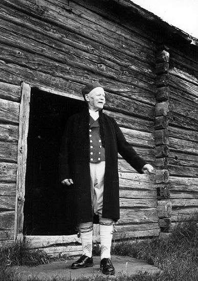 """""""Nittaho-Jussi"""" Johannes Johansson i Nyskoga sockendräkt träder ut ur rökstugan på Rautalampi hembygdsgård en morgon efter vedskvickande nattläger där."""
