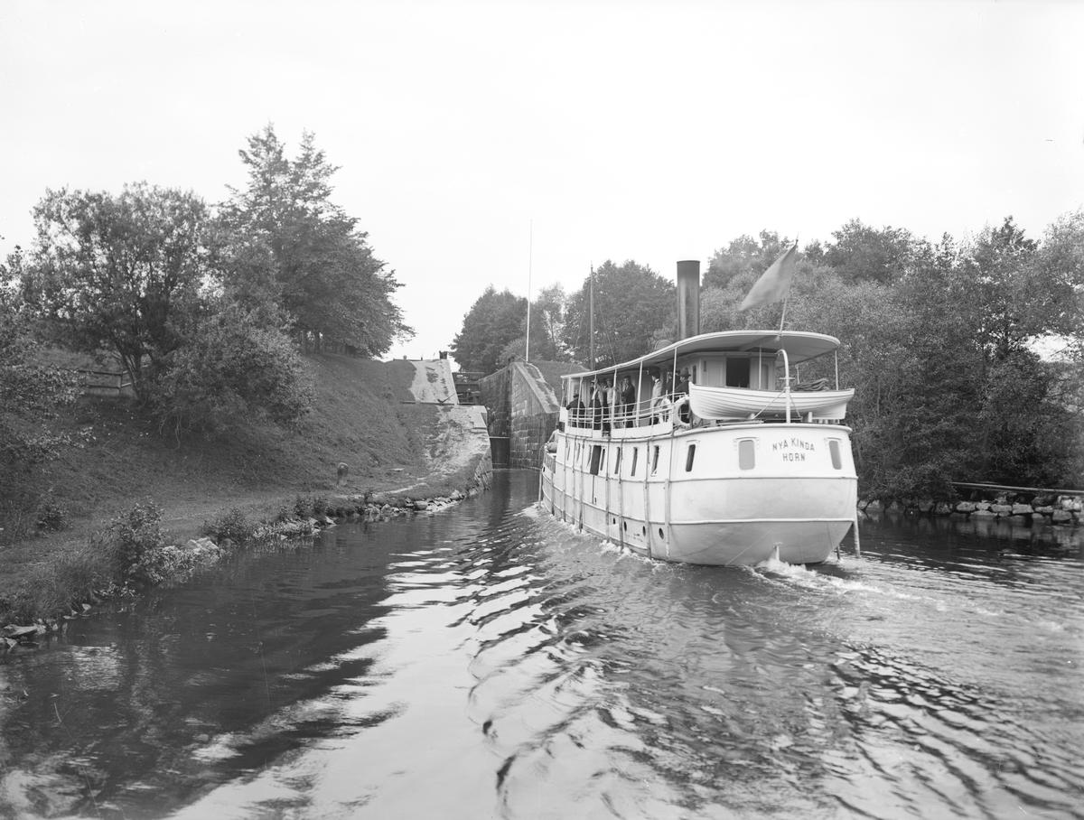 Passagerarfartyget Nya Kinda stävar in mot Hamra sluss. Fartyget seglade på kanalen mellan åren 1896-1912. Hon var beställd av Ångfartygsbolaget Linköping-Horn och byggd på Mälarvarvet i Stockholm.