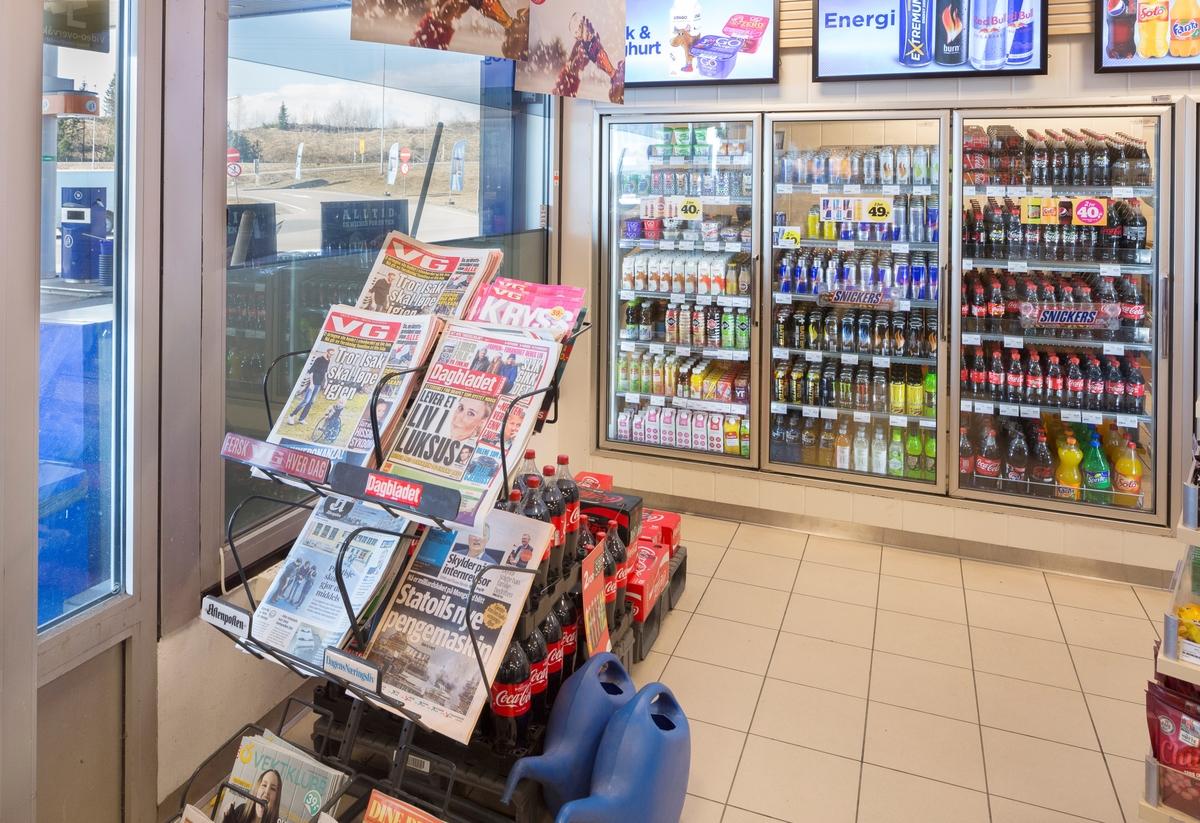 Statoil Dal. Butikk interiør med avisstativ ved inngangsdør.  I bakgrunnen en veggseksjon med kjøleskap med leskedrikker og melk. Reklameskilt over kjøleseksjon og en pal med colaflasker på gulvet.