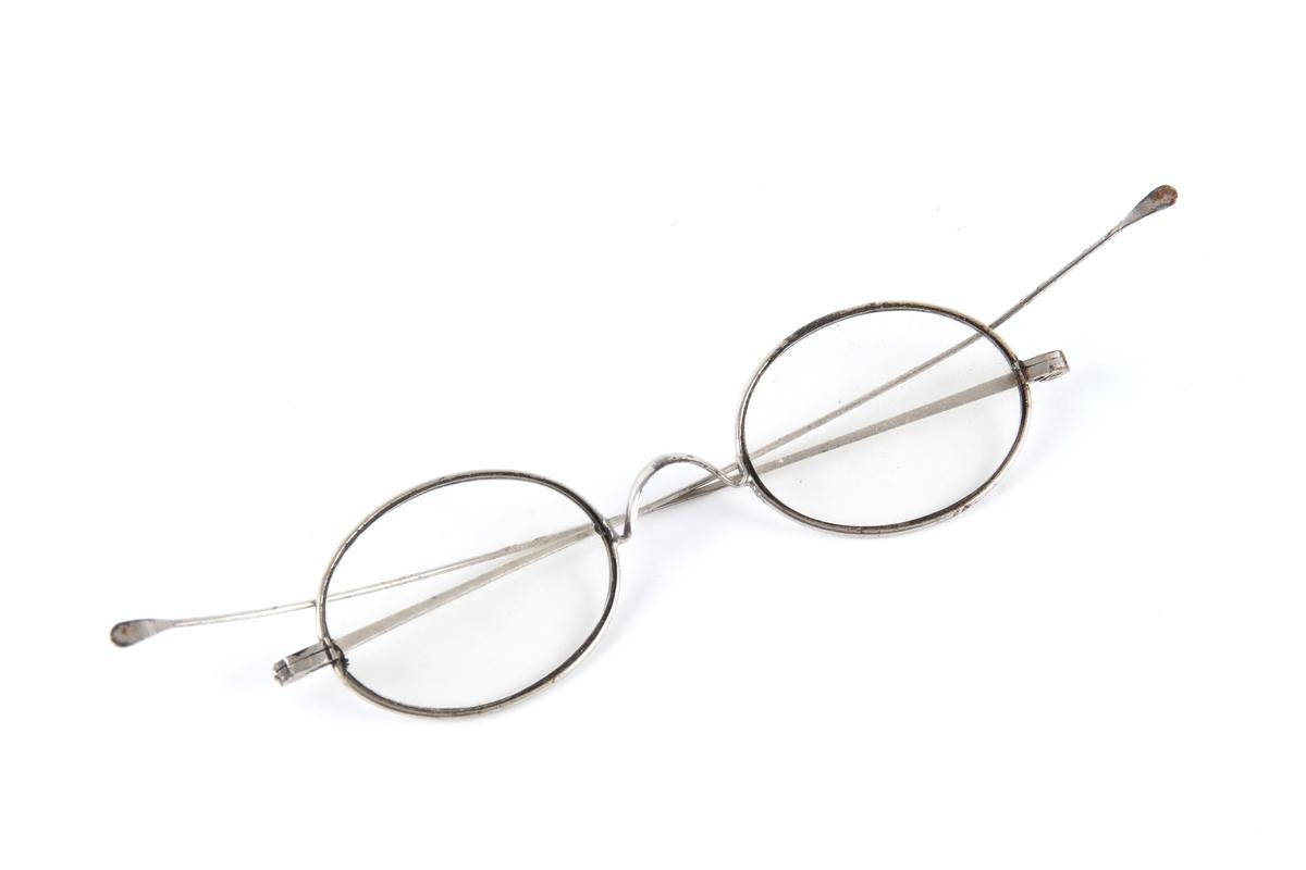 Brille med ovale glass. Tynn metallinnfatning med hengsler og to stenger.