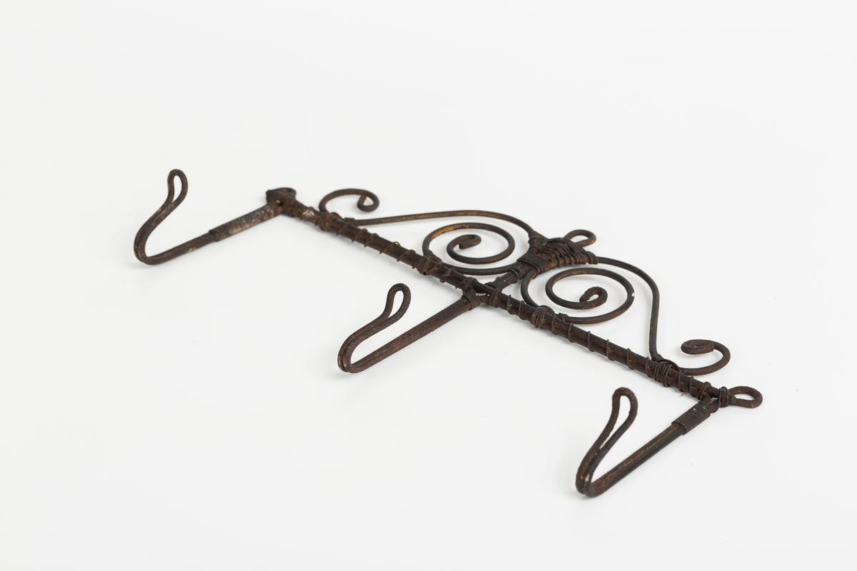 Knaggrekke med tre knagger laget i ståltråd. Tykkere ståltrå danner knagger, opphengsløkke og ornamentikk over knaggene. Tynnere tråd binder og låser den tykke tråden på plass. Ornamenter i form av trådspiraler over knaggene. Opphengsløkke øverst på midten og ytterst over endeknaggene.