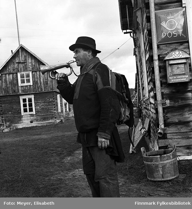 Fotograf Elisabeth Meyer har fotografert postfører Anders Nilsen Slangeng fra Karasjok.  Anders Nilsen Slangeng poserer med posthornet og postsekken på ryggen, foran et postkontor. Anders var ektemann til Berit Pettersdatter West. Hans foreldre var Nils Andersen Badjenjarg (småbruker) 1851-1917 og Anne Aslaksdatter Gaino (1855-1898). I Geni er han oppført som korporal, småbruker, postfører og predikant. Født 2.februar 1882 (torsdag) på Karasjokfjellet, Karasjok, Indre Finnmark, Norge. Død 28.juni 1973 (torsdag) på Karasjok sykestue, Karasjok, Indre Finnmark 91 år gammel. Han bodde i Badjenjárga, Karasjok kirkested.