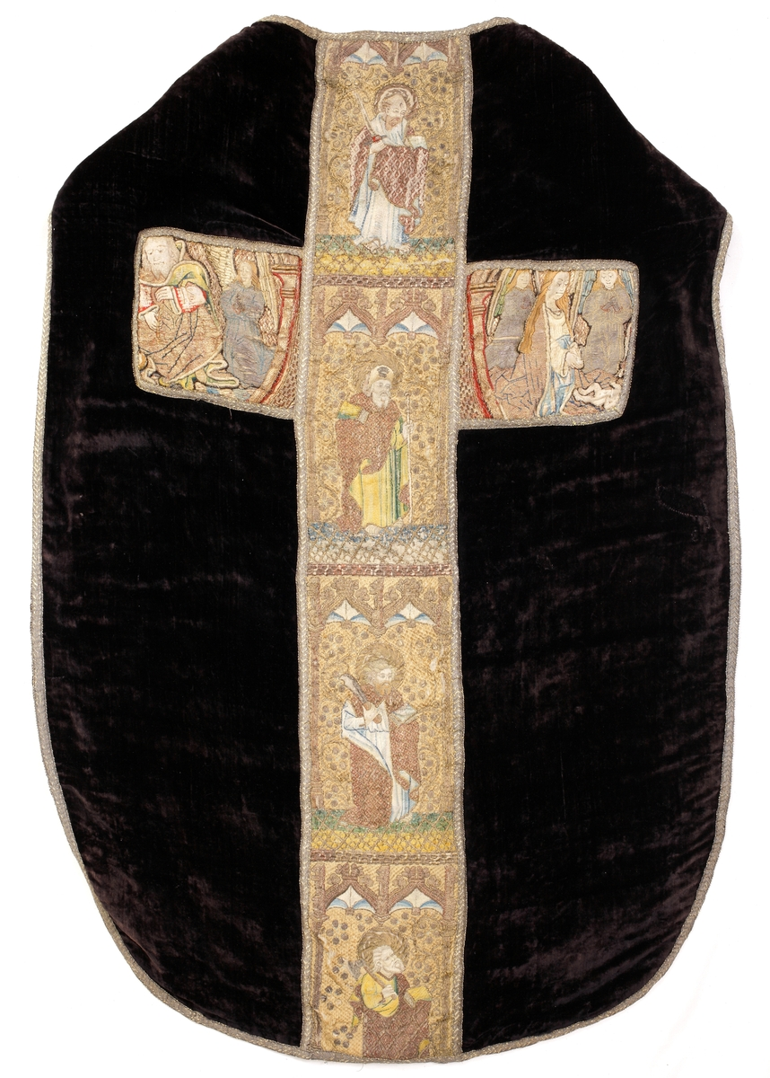 Mässhake av svart sammet. Korset broderat med guld, silver och silke. Den lodräta bården framställer apostlarna Paulus, Jakob d.ä., Bartolomeus och Matteus. Lübeckarbete omkr. 1475. Korsarmarna utgör delar av en ryggsköld med framställning av Kristi födelse, utförd av annan tysk skola omkr. 1500.  Broderierna är utförda i silke, samt guld- och silvertrådar. Som broderibotten är ett oblekt tuskaftvävt linnetyg använt. Fodrad med ett nyare brunt tuskaftvävt linnefoder. Vid montering har skölddelarna förväxlats så Maria tittar bort från mitten i höger del och Josef tittar åt andra hållet. Jesusbarnets kropp har delats och ligger i respektive nedre yttre hörn.