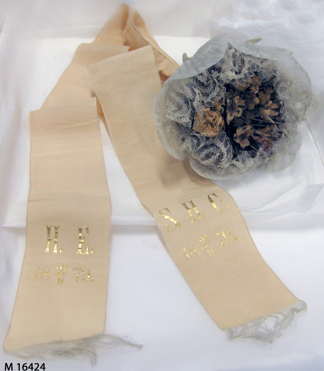 """Brudbukett med blandade blommor monterade med hjälp av ståltråd till en kompakt bukett, och sedan klädd med (inifrån och ut) cremefärgad broderad silkesslöja, plisserad organdi och ytterst """"hylleblad"""" av organdi formade med ståltråd, några även med tygblommor. Ett guldmönstrat vitt papper klär handtaget som bildas över stjälkarna. Ett brett ripsvävt sidanband är sedan knutet runt handtaget och ändarna bildar två nedhängande band med signaturer målade i guldfärg på båda: S.H.C 18 27/9 79 respektive H.E. 18 27/9 79."""