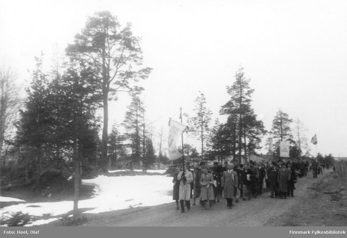 Elever og lærer fra Finnmark off. Gymnas i Alta går i 17. mai tog.   Olaf Hoel (1903-1970) var den første rektoren ved fylkets første gymnas Finnmark off. Gymnas i Alta i årene 1948-1952. Kjell F. Hoel har gitt en liten bildesamling etter sin far fra hans tid i Alta til Finnmark fylkesbibliotek. Olaf Hoel gjorde en pionerinnsats for skolen under gjenreisningen av landsdelen etter krigen.