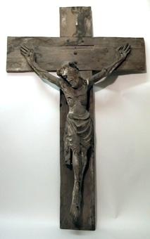 Krucifix, där kristusbilden är fästad på ett kors av breda plankor. Längs kanterna på korset finns skurna konkava ovaler. Korset är avsågat i alla ändarna. Figuren är massiv. Främre del av fot och mindre delar är anstyckade. Endast få kritgrundsrester är bevarade.