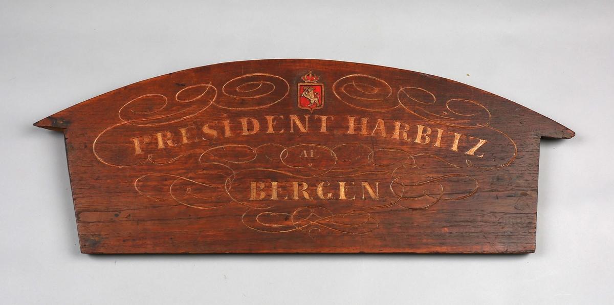 Bakstykket av jigg tilh. bark PRÆSIDENT HARBITZ. Bakstykke av tre dekorert med skipets navn og det norkse riksvåpen.