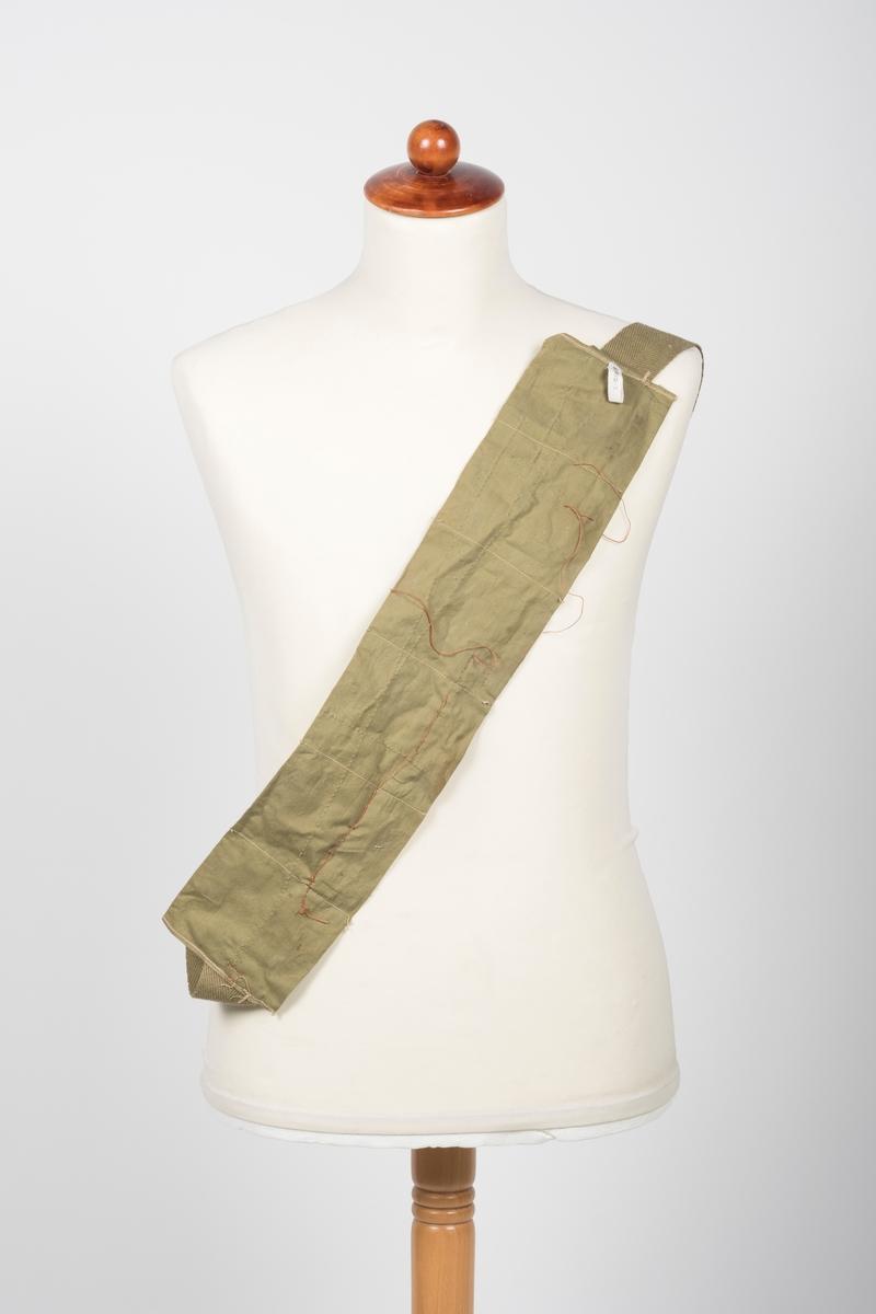 """Militærgrønt ammuniasjonsbelte med seks """"lommer"""" og påtrykk """"CAL. 30 BALL M2 8RD CLIPS T.W. 19633"""" på hver side. En rødbrun tråd med ukjent funksjon er sydd gjennom lommene.  Hver lomme er 8,5-9 cm bred og 10,5 cm høy."""