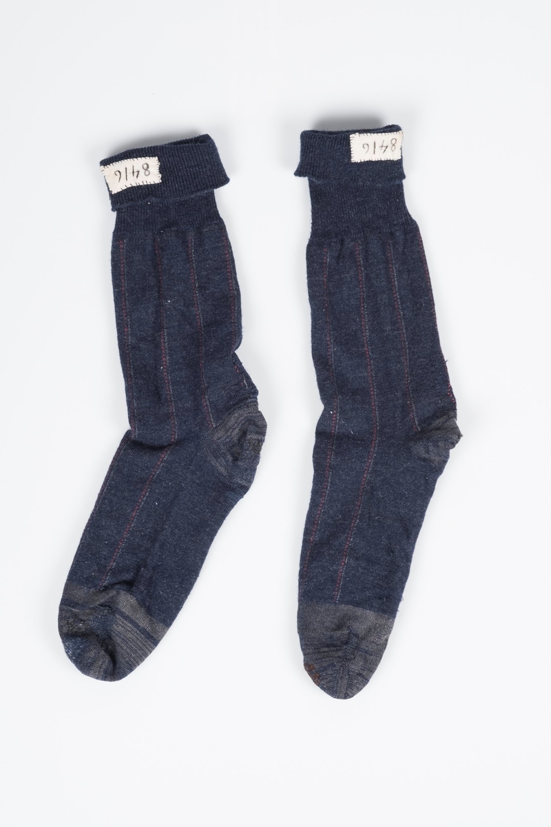 Mørkeblå høye sokker, med grå detaljer og røde og hvite striper. Sokkene er meget godt brukte og stoppet flere ganger. På innsiden øverst er det sydd inn en lapp med fangenummeret 8416, som identifiserer sokkene som Erich Mønnichen Plahtes.
