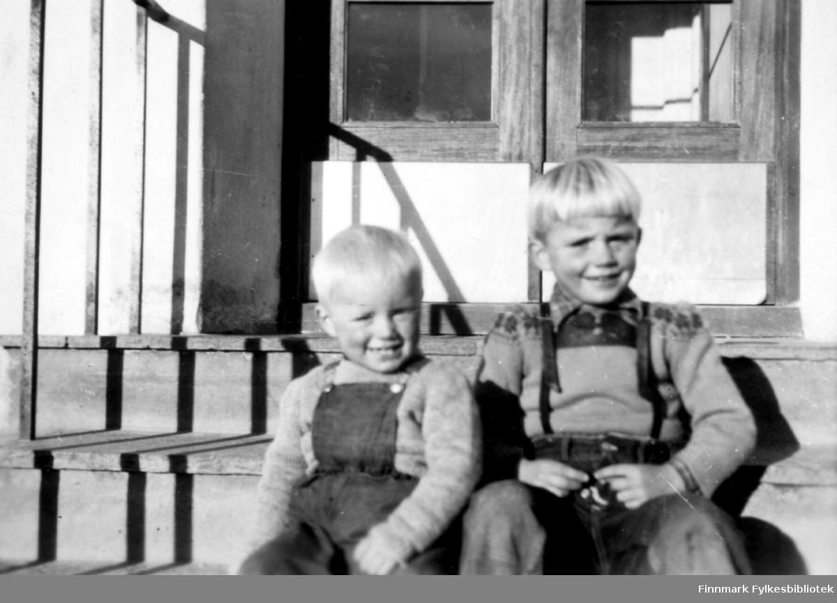 Tor og Kjell Klemetsen. Begge gutter fotografert sittende på trapp med dobbel inngangsdør i bakgrunnen. Gutten til venstre i snekkerbukse/selebukse og gutten til høyre i bukse med bukseseler. Begge har ullgenser.  Familiealbum tilhørende familien Klemetsen. Utlånt av Trygve Klemetsen. Periode: 1930-1960.