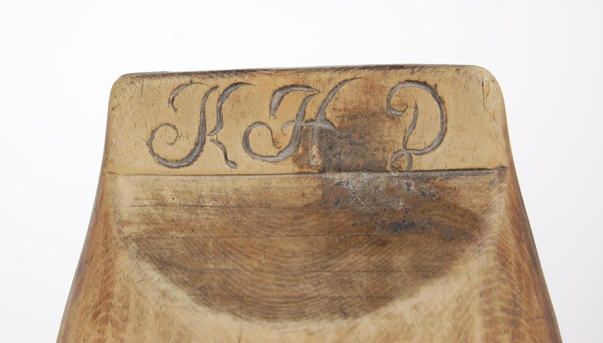 Trakt av bjørk. Avlang form, oval. Begge kortsidene har utskjæringer og innnskrift under.