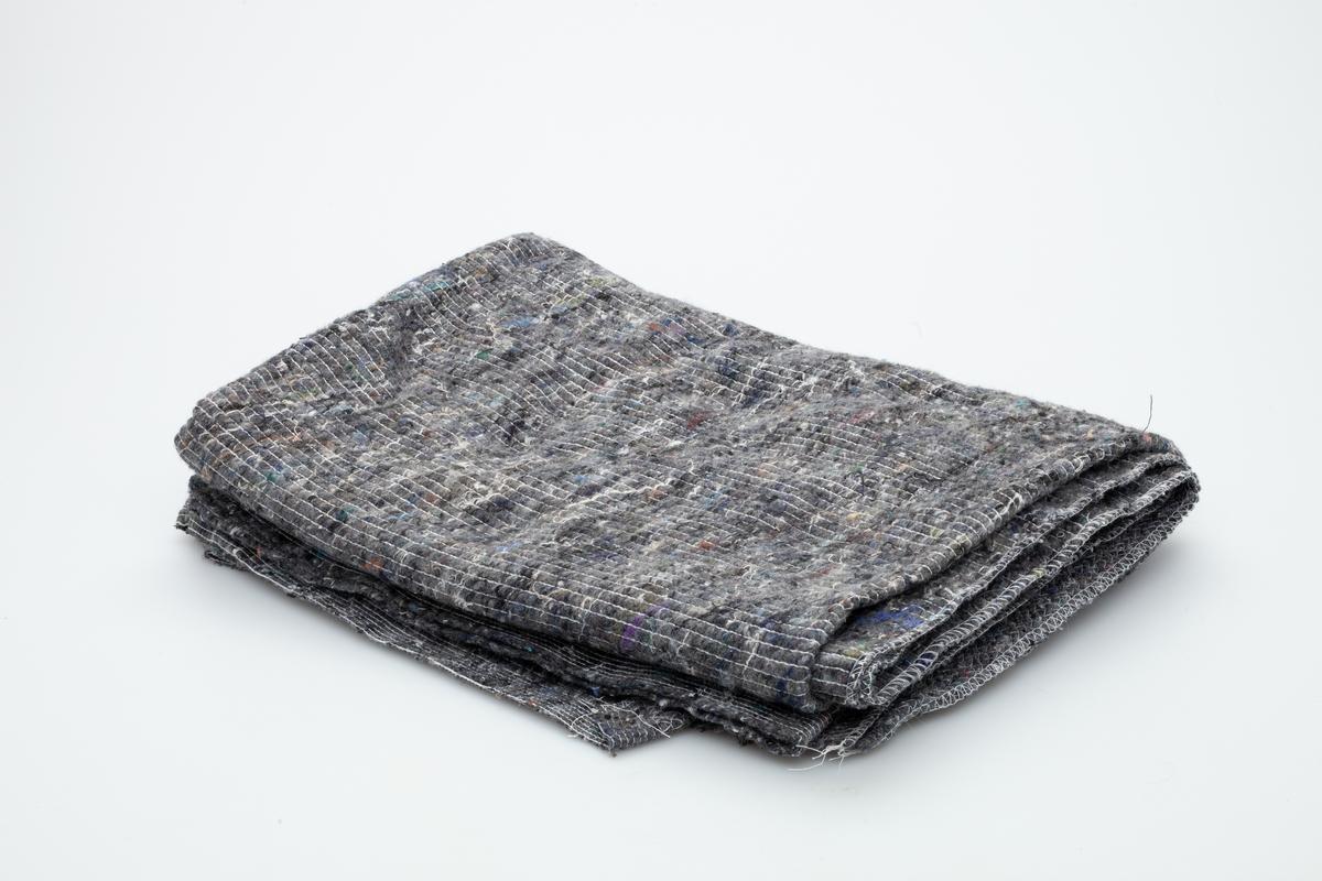 Et billig grått fleeceteppe.  Gjenstanden er samlet inn i forbindelse med Hundeprosjektet 2006-2007 Husdyr på museum - Et fellesprosjekt i Akershusmuseet 2007