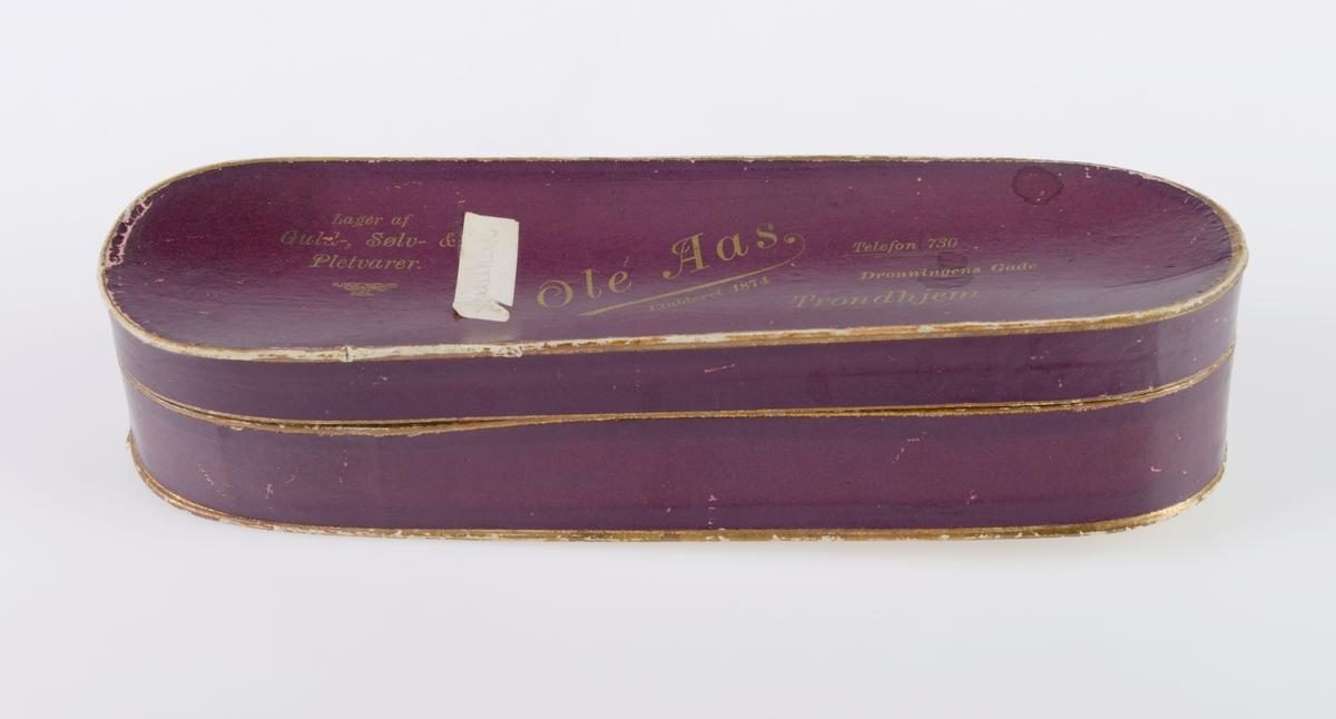 """To esker med avtagbart lokk laget av papp. Eskene er avlange og er avrundet i begge endene. På utsiden er eskene trukket med burgunderfarget papir. Oppe og nede på både eske og lokk er det en enkel gullstripe. På lokket er det trykt på tekst i gull og på undersiden er det påskrift med blyant, se """"Påført tekst/merker"""". På lokket til FTT.56046.02 er det pålimt en papirlapp med blyantskrift. Det er vanskelig å tyde hva som står på den. Innvendig er esken hvit. Eskene er fra gullsmed Ole Aas."""