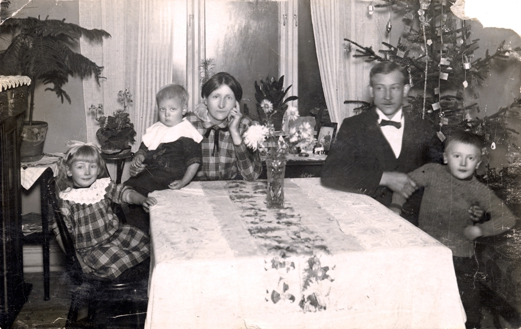 Familjen Träff sitter runt ett matbord i ett rum med julgran. Från vänster Agnes, Thore, Mariana, Oskar och Helge.