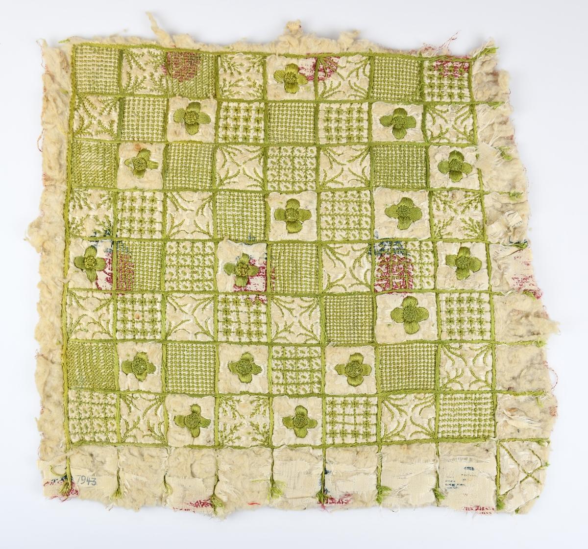 Anmärkningar: L. 310. B. 310. Täcke/delar. Fyra delar klippta ur ett täcke. Vitt sidenbroderi av grön silke, ett rutnät ca 3x3 cm mer eller mindre fyllda rutor med yttäckande broderi och blommor. Sidentyget, slitet, har ivävt rött mönster. Fodertyg av glest oblekt bomullstyg med vegetativt mönstertryck i rött. Mellan tyglagren ett lager vadd. Låg i svepask inventarienummer 9790.