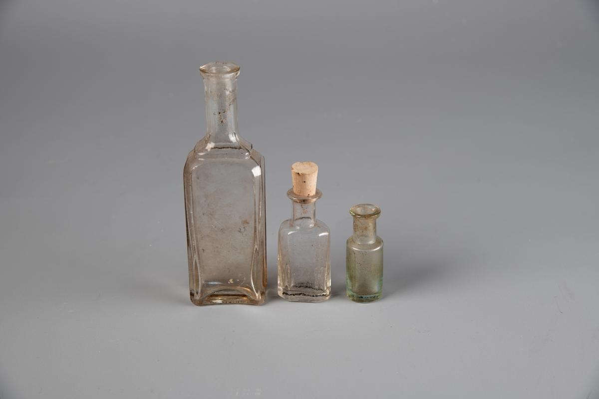 Tre glassflasker med innsnevring til halsen. Rundt hals. A er firkantet og rett, med en rundt hals og ingen kork. B har kork. C er den minste flasken med lett utsvunget kropp. Ingen kork.
