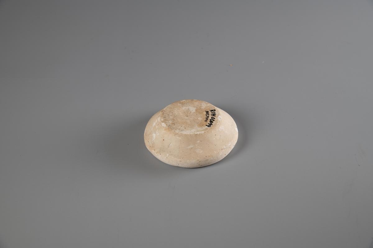 Rundt gipsform. Formmotivet er en halv valnøtt. Valnøtten er 2,7 cm lang på sitt lengste.