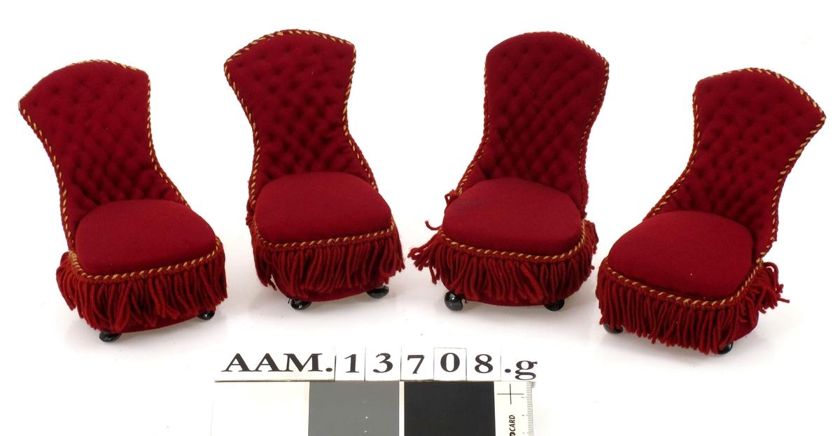 Overstoppet, med burgunderrødt ulltrekk, gule skrå korssting.  Består av sofa, chaisselongue, to lenestoler, to litt større og fire mindre stoler uten lener.  Alle laget av papp, med sorte kulebein.    a: Sofa b: Chaiselongue c - d:  Lenestoler, 2 stk. e - f:   Stoler uten lener, 2 stk.  g - j:   Stoler uten lener, 2 stk.