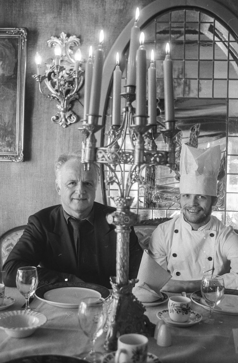 Villa Sandvigen, far John Normann Pedersen og sønn med kokkelue, sitter i restauranten ved et pent dekket bord.