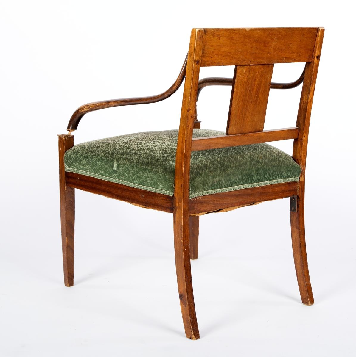 Sen-empire stol, opprinnelig med to armlener, men ett er slått av. Armlenene er mørkere enn resten av stolen. Dreid kloss som forbinder armlenet til stolbeinet mangler. Trukket og stoppet sete. Svakt buede bakbein. Intarsia i tverrstykke og ryggbrett, klassiske figurmotiv og fabeldyr. Antikk-inspirert. Samme motiv på alle stolene, men med små ulikheter. Også samme motiv på skapene til sofaen, men ser ikke ut til å være samme kunstner. Enkel intarsia i de to fremste stolbenene, rutemønster, og en stripe i listen under stolsetet. Del av møblement.