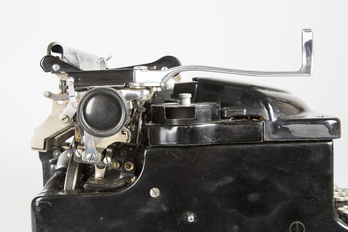 Rektangulær mekanisk Amerikansk-produsert skrivemaskin fra ca. 1900. Høy og tung modell. Står på fire gummierte føtter.