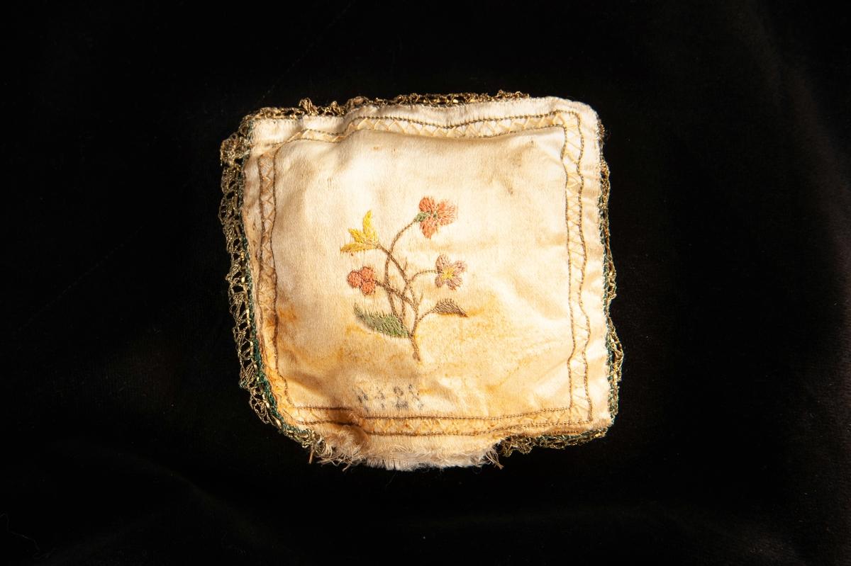 """En liten stoppad och broderad kudde i benvitt siden. På framsidan dekorerad med en broderad präst, omgiven av s.k. """"käpp och krycka"""" i delvis förgyllt silver, fastsydda i benvita sidenrosetter. Broderad bård(zick-zack) i beige och ljusgrönt. På baksidan en liten broderad blomsterbukett i rött, gult och grönt, med likadan bård som på framsidan. Längs kuddens kanter fastsytt en guldbård i metalltråd."""