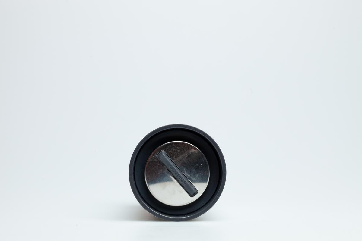 Et sort skrulokk i hard plast. Lokket har en blank overdel.