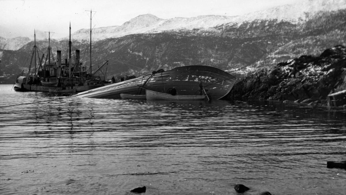 Berging av kantret skip fjæresteinene, samme fartøy som BSJ 2018-003-003. To store motorskip i bakgrunnen. Kystlandskap om vinteren.
