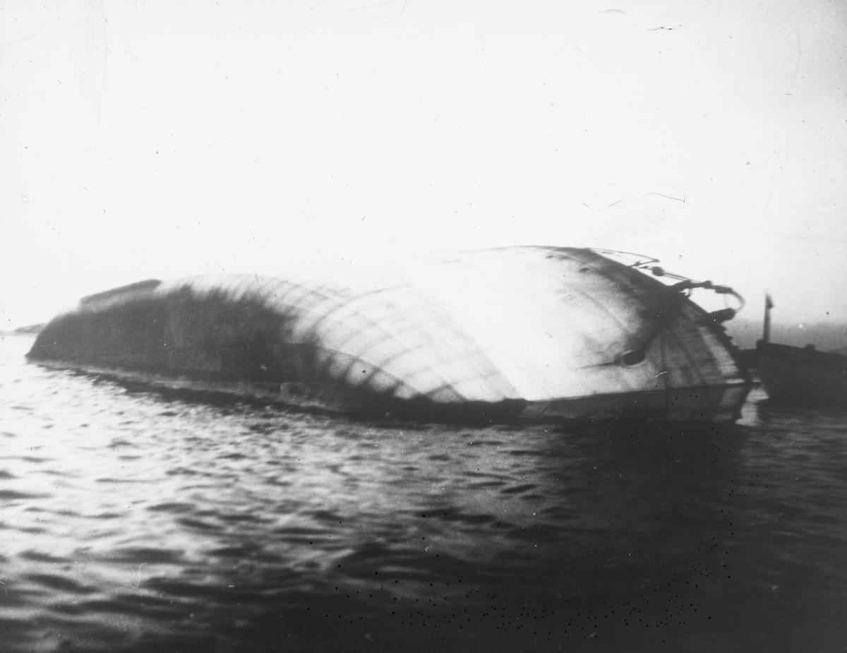Skipsvrak som har kantret. Kun skipssiden stikker opp fra vannet.