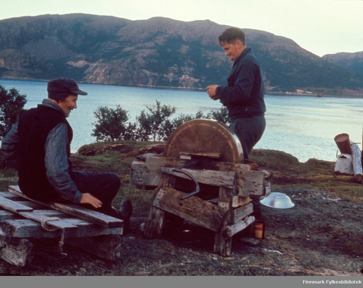 """Kunes, sommeren 1964. I bukta på vestsiden av Storelva.Per Ole Andersen Matus (Varanger-Ola) sitter ved slipesteinen, mens Edvard Johansen studerer om kniven er slipt godt nok. Per Ole Andersen Matus er registrert født i 1891 i Nesseby. Foreldre er Anders Henriksen Matus, født 1834 i Enare Finland og Bigga Persdatter, født 1862 i Nesseby. De er registrerte i 1900 som fiskere og gårdbrukere.  Kunes (samisk: Gussanjárga) er en bygd i Lebesby kommune i Finnmark. Stedet ligger innerst i Storfjorden. Fylkesvei 98 passerer igjennom Kunes. Fotografen, Richard Bergh, har også skrevet et hefte som heter: """"Når vi sitt' her og prate"""". Folk i Laksefjord forteller. Norsk Folkeminnelags skrifter nr. 122. H. Aschehoug & Co. (W. Nygaard). Oslo 1980. ISBN 82-03-10187-9"""