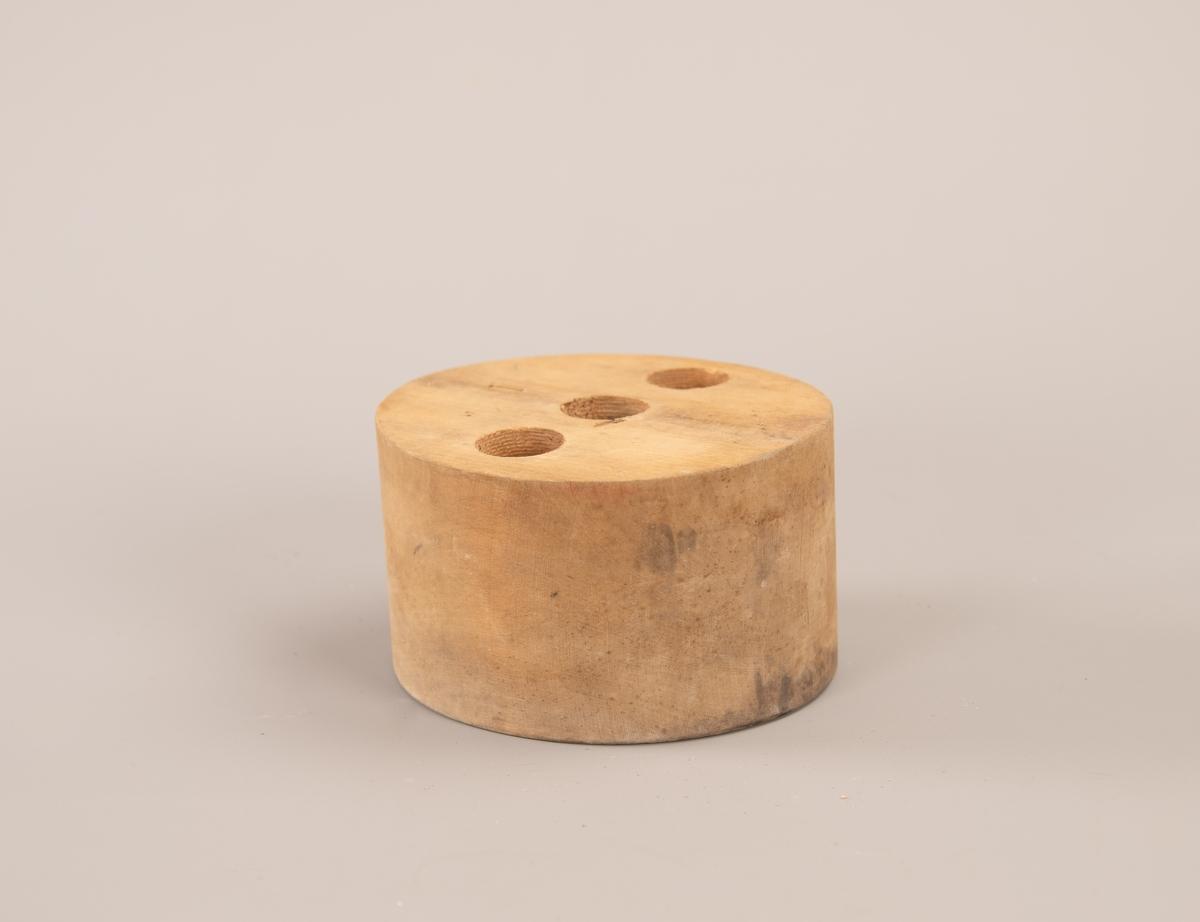 Oval hatteform med tre like store hull boret inn på oversiden. Hullene er 4,5 cm dype.
