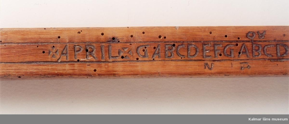 KLM 1650. Runstav. Kalenderstav. Liksidig fyrkantig stav av trä, i båda änderna rak avslutning med mässingsbeslag. I stället för runor användes de latinska bokstäverna A B C D E F G, endast i slutet på ena sidan förekommer en rad runor: På en sida är inskuret: Ao 1576 + D:I:IAN. ( falsk datering ).