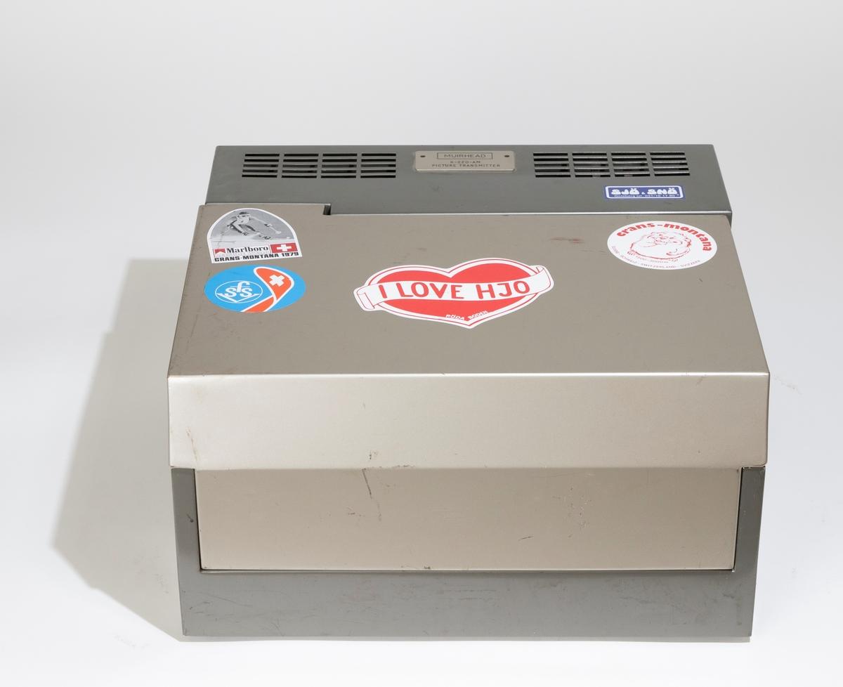 Telefotoapparat för fotografisk överföring av bilder över telefonnätet av märket Muirhead  K-22-AM Picture Transmitter. Apparaten har en fyrkantig form med ett hölje av metallplåt. Den öppnas med en löstagbar huv. Upptill sitter en lucka för ytterligare öppning av apparaten. I apparaten finns en liggande metallcylinder för fastsättning av bilden på, en grön telefonlur av plast, panel med knappar och reglage. Till apparaten hör en elsladd, en telefonsladd och bruksanvisning på ett pappersark. På huvens utsida sitter flera klistermärken.  JM 55367:1, telefotoapparat JM 55367:2, huv JM 55367:3, elsladd JM 55367:4, telefonsladd JM 55367:5, bruksanvisning