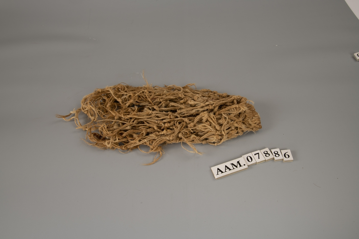 Frynser av tvunnet lin eller hamp,  knyttet antagelig til et skjørt eller annet plagg.