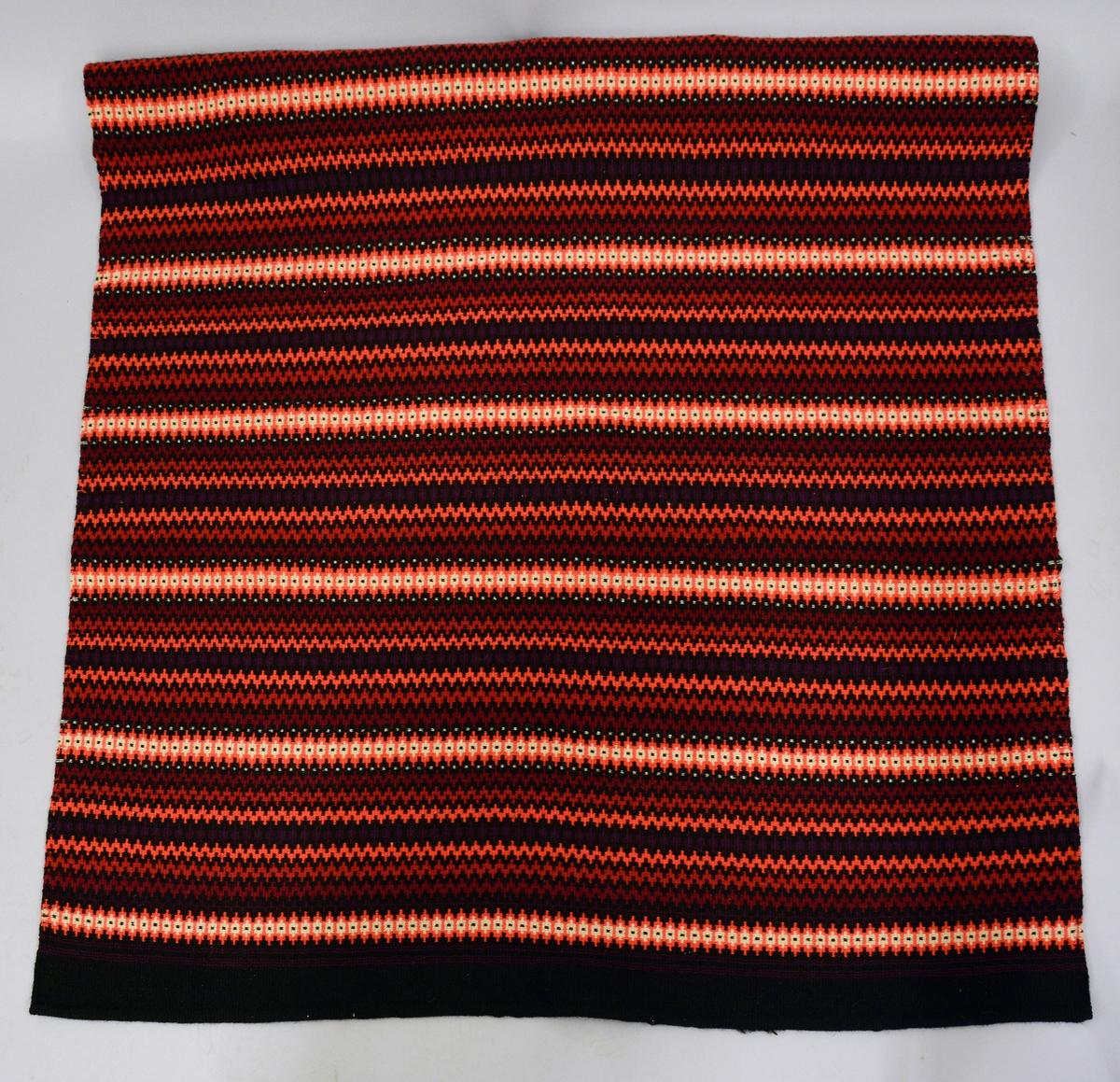 Fra protokoll: Åkle i krokbragd, i 7 like mønsterrapporter à ca. 20 cm. 2 tråds Rauma spelsaugarn. Sort (636), rosa (657), rødt (644), beige (692), to fiolette farger, den ene noe mørkere enn 675 og den andre noe mørkere enn 637. Mål: 168 cm X 128 cm.