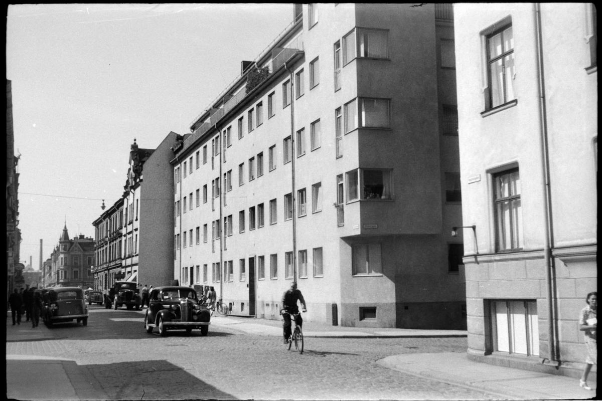 Bil och cyklist på kullerstensgata i Norrköping.