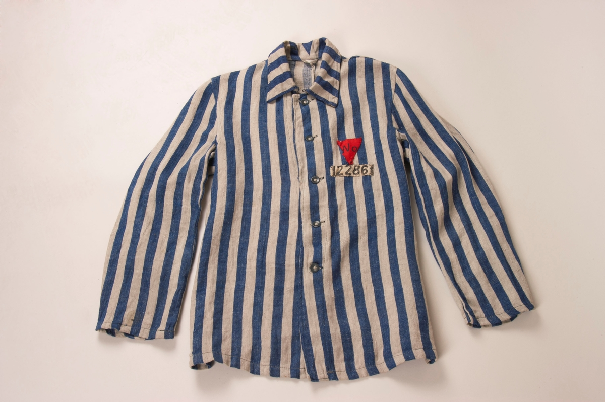 """Blåstripet skjorte med lange ermer. Skjorten har krage, og kan kneppes sammen med fem knapper på midten foran. Øverst er det en hempe i metall som fester skjorten ytterligere ved halsen. I nakken er det sydd på en hempe for oppheng. Skjorten har ekstra søm på sidene, muligens for å bedre passformen. Skjorten har også en søm midt på ryggen.  Materialet ser ut til å være en blanding av ulike fibrer. Skjorten har ingen lommer. Fargen ser falmet ut, det er stor forskjell mellom fargen generelt og fargen under nakkekragen, som nesten framstår som lilla.    Nummeret er fangenummeret Julius Paltiel fikk i Buchenwald. Påsydd rød trekant med bokstavene """"No"""", som står for """"Norge""""."""