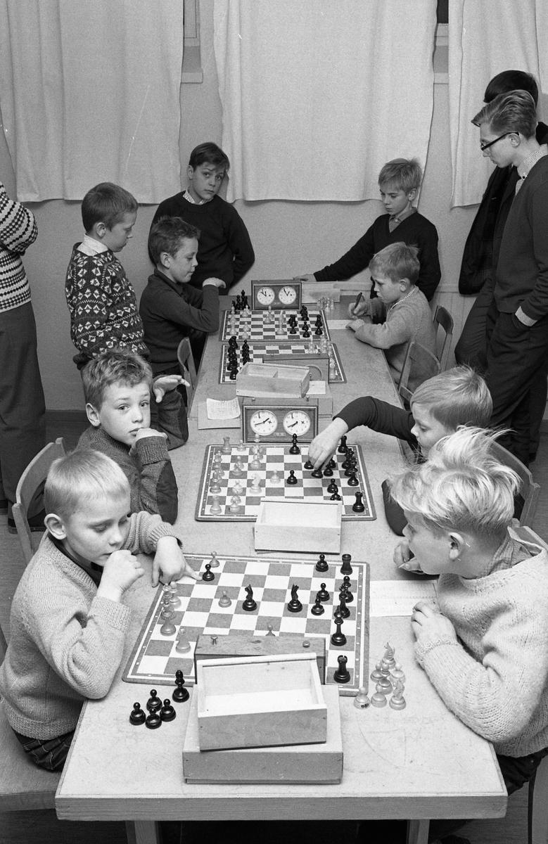 AT-schack. Tre schackpartier pågår. Spelarna är pojkar. De sitter vid ett långt bord. Några tittar på. Pojken till höger, med handen på elementet, är Ulf Andersson.